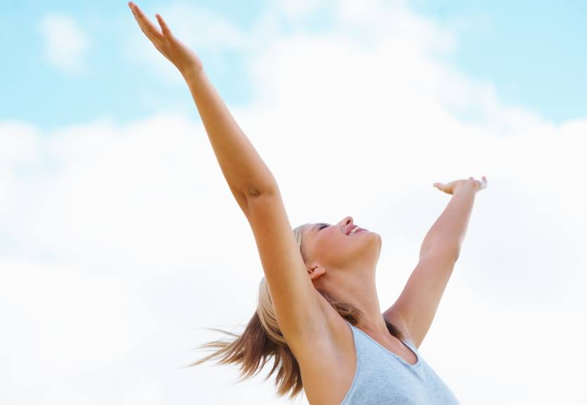 Happy woman with arms up in the air