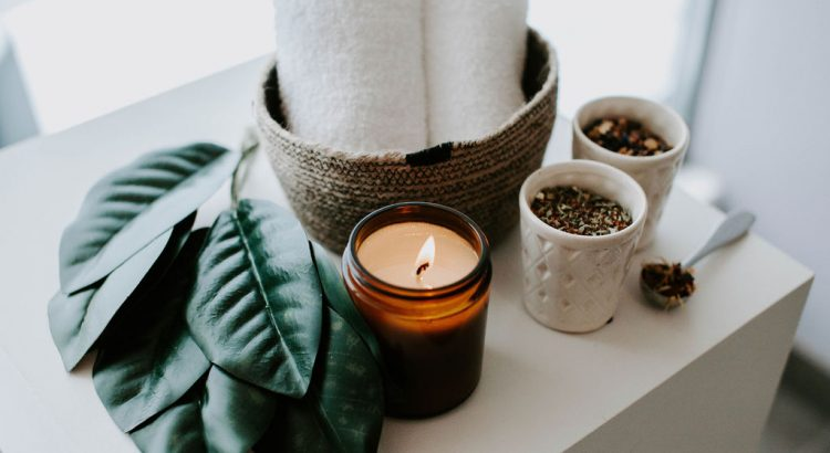 candle with towels, leaves & tea